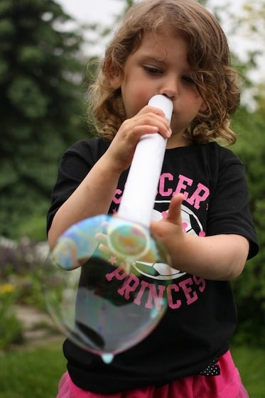 child blowing bubble with cardboard tube