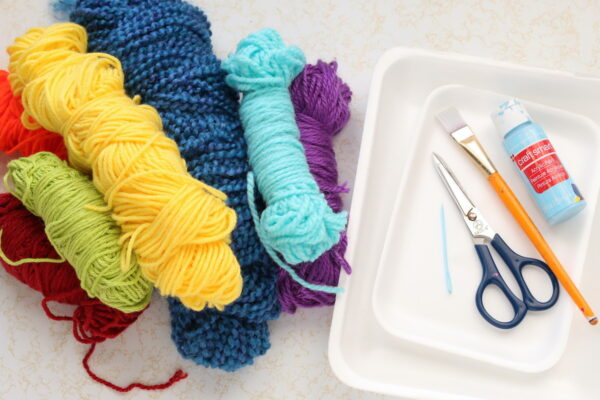 yarn, scissors, plastic sewing needle, styrofoam produce trays