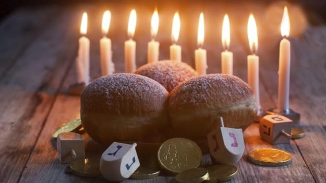 Menorah, donuts, chockolate coins and wooden dreidels. (Credit: Karaidel/http://www.istockphoto.com)
