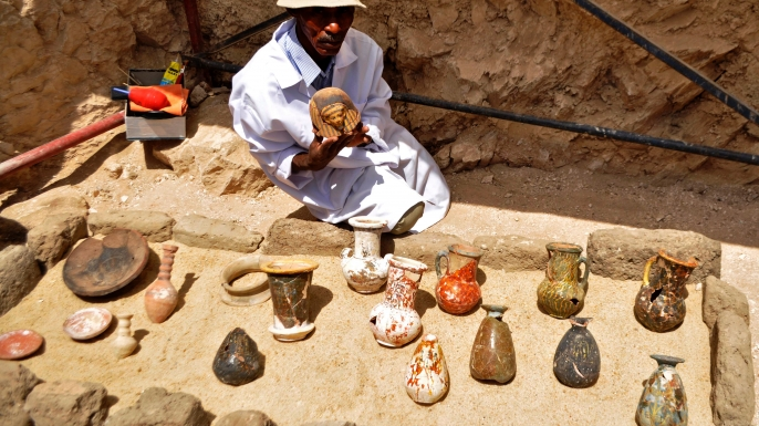 A member of an Egyptian archaeological team shows artifacts discovered in a 3,500-year-old tomb in the Draa Abul Nagaa necropolis. (Credit: STRINGER/AFP/Getty Images)