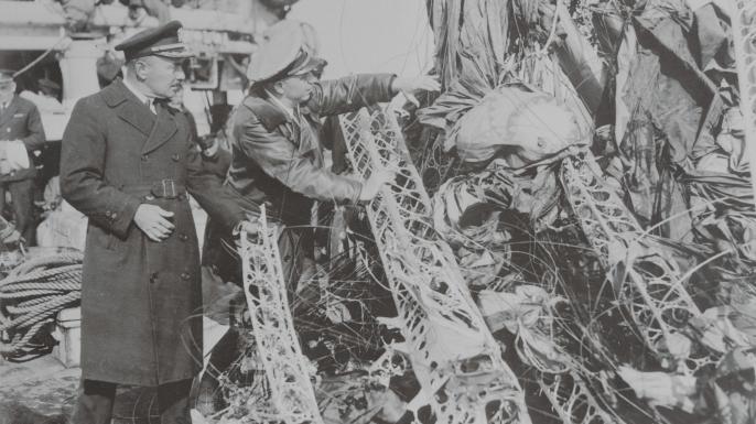 Capitán R.A. Blanco, (izquierda) a cargo de las operaciones de salvamento, y Teniente. El comandante J. L. Fisher, experto aéreo de Lakehurst, N.J., examina la enorme masa de restos del dirigible dirigible de los Estados Unidos, después de haber sido extraída del océano por los EE. UU. Barco de salvamento Falcon. (Crédito: Bettmann / Getty Images)