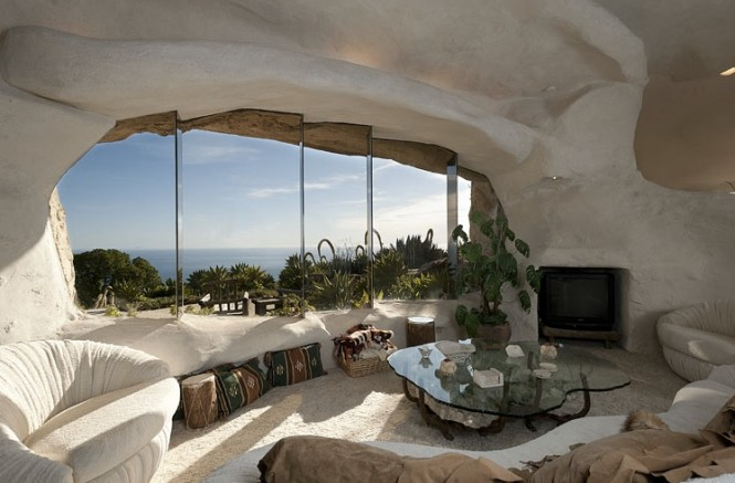 The interior of the Stone Age styled pad is linked to exterior beauty by way of large expanses of glass nestled in naturally irregular shaped surrounds, frameless and organic in appearance, through which the tantalising views of sea and mountain can be absorbed.