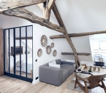 The first apartment is in the heart of Marais and measures 50 square meters (538 square feet). Exposed wood beams from the original structure really pop against white walls for an effective eclectic design. Natural materials are used throughout the space to play off of these stunning means. A solid walnut wall conceals the practical spaces of the house while class separates out the bedroom, allowing plenty of sunlight to filter into this top floor apartment.