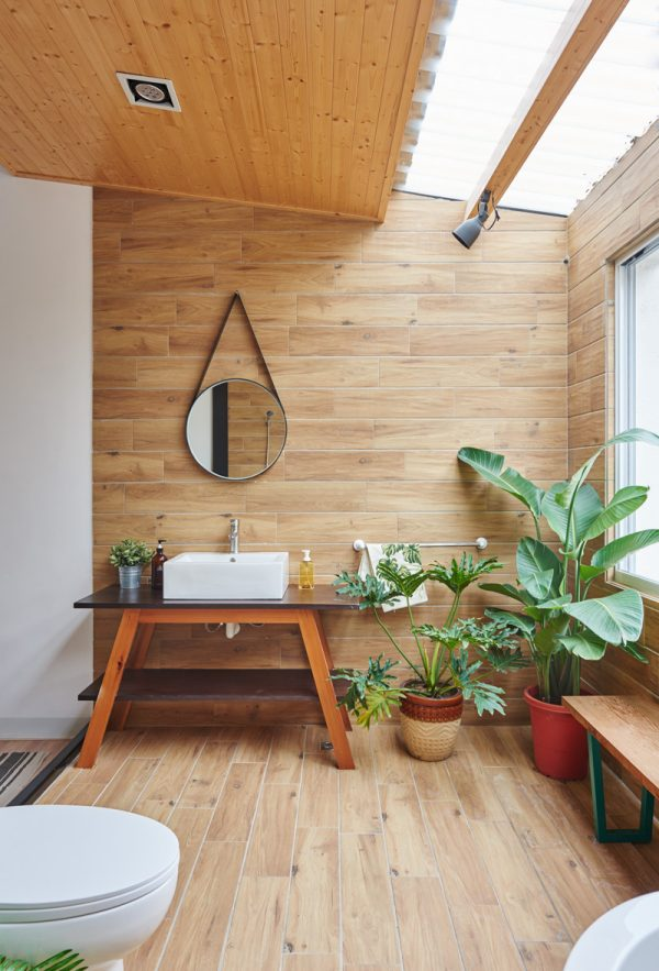 Lush plant life and a teardrop mirror in the bathroom add a Scandinavian cabin feel that feels both global and particular. Full wooden floors, ceilings and walls give the experience of being in another world, while wide-paned windows let the outside world in.
