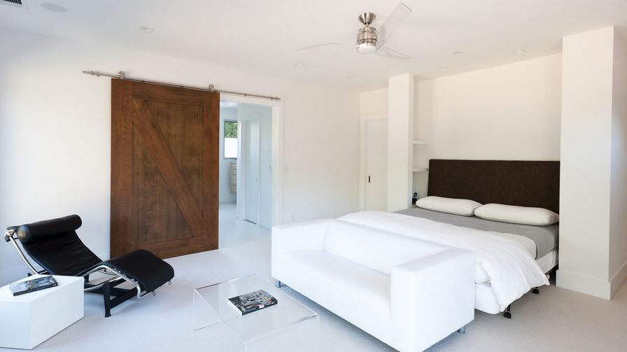 Minimalist bedroom featuring a siding barn door