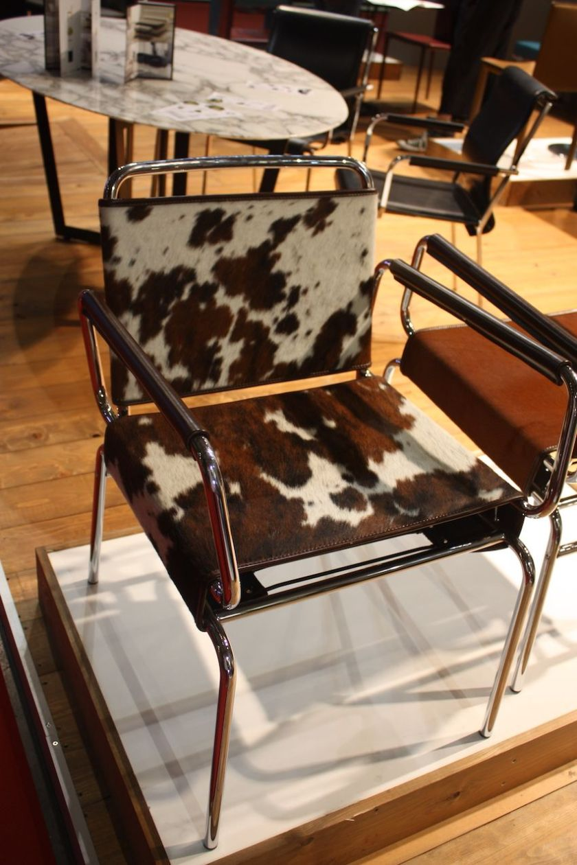 This armchair has a tubular steel chrome-plated frame covers in pony hide covering. It's a casual and fun armed leather dining chair from Artleather.