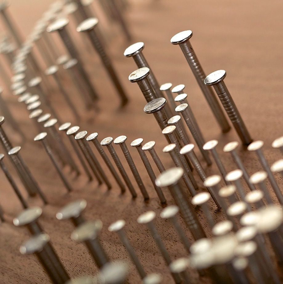 A design made of nails before they are cut flush with the table.
