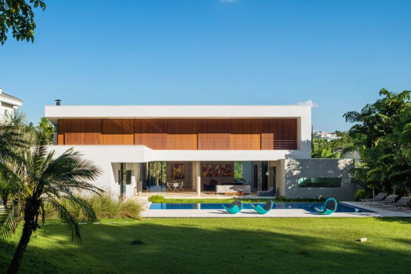 The rear side of the house is open towards an infinity edge swimming pool framed by a sleek patio