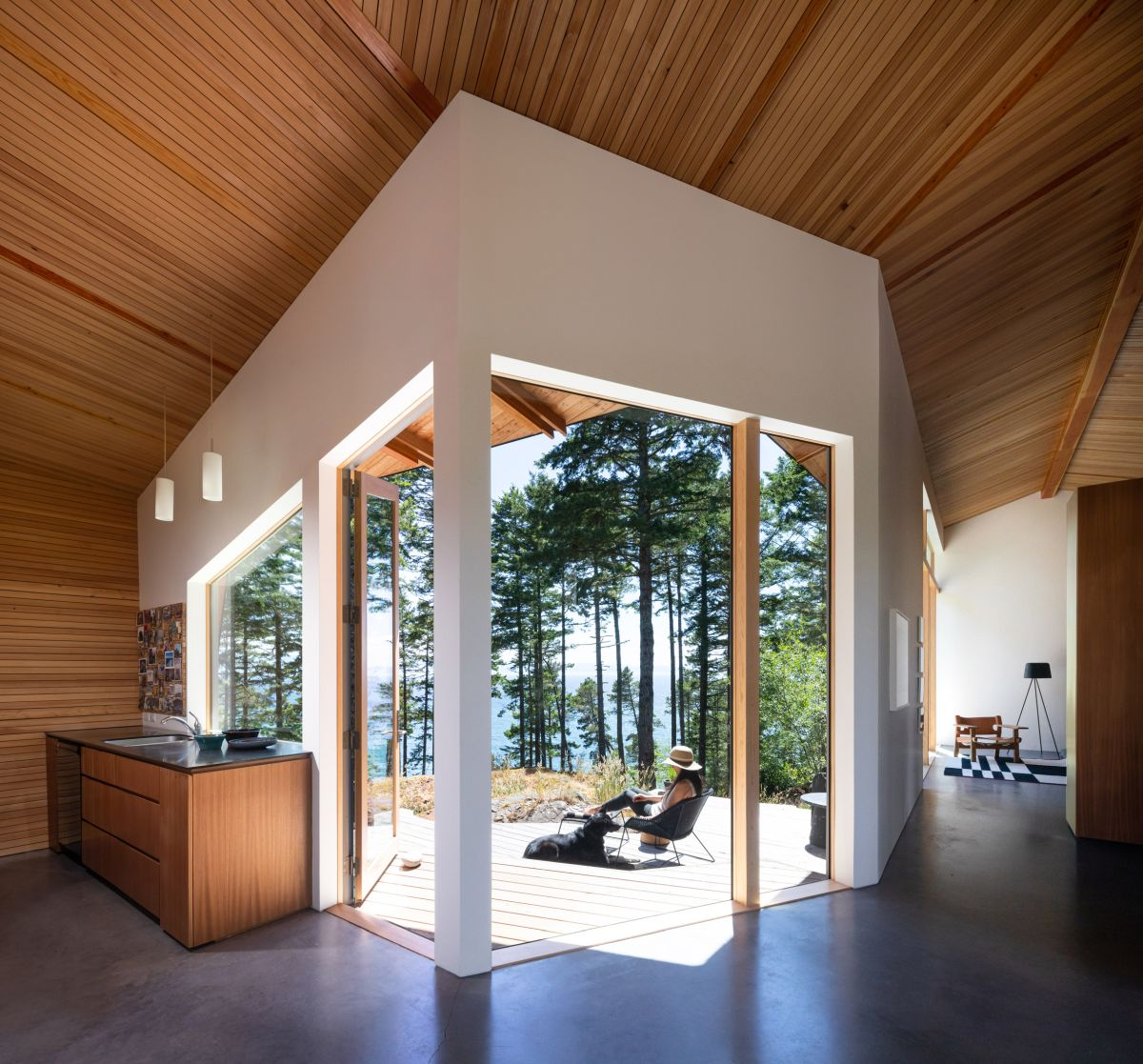 The geometric layout exposes the central section of the house to the forest and even gives a glimpse at the sea