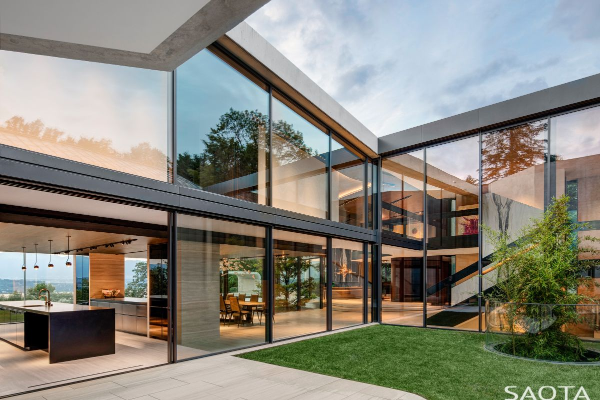 Full-height windows and sliding glass doors open up the internal spaces to the beautiful garden and the views