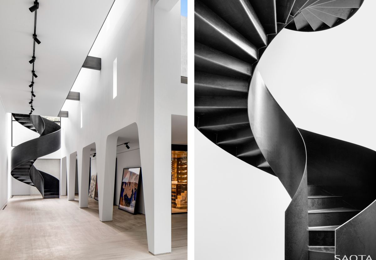 A black spiral staircase connects these sections of the house without wasting space