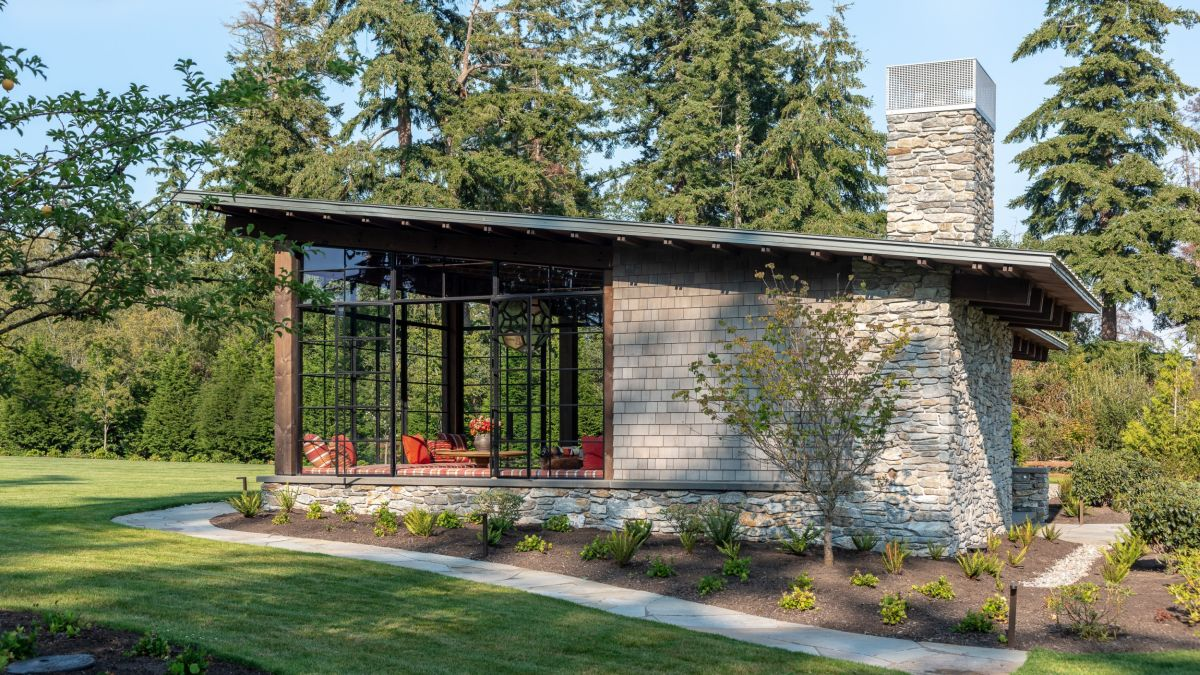 The house is framed by flower beds which help to make it look more natural in this context