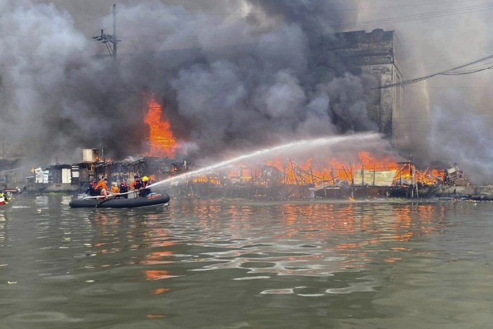 Philippine coastguard staff use a rubber boat as they try to extinguish a blaze caused by a cargo ship explosion. Photo: AP