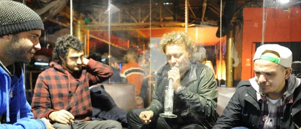 """Des participants au """"Cannabis Cup 2015"""" fument de la marijuana, le 19 juillet 2015 à Montevideo ( MIGUEL ROJO (AFP) )"""