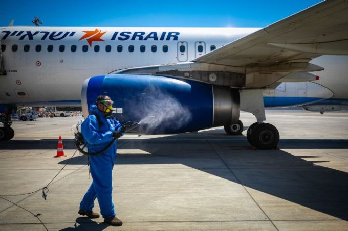 A worker wearing protective clothing disinfects an Israir plane at the Ben Gurion International Airport near Tel Aviv, on August 17, 2020.