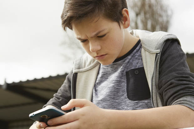 Teenager hunched over phone