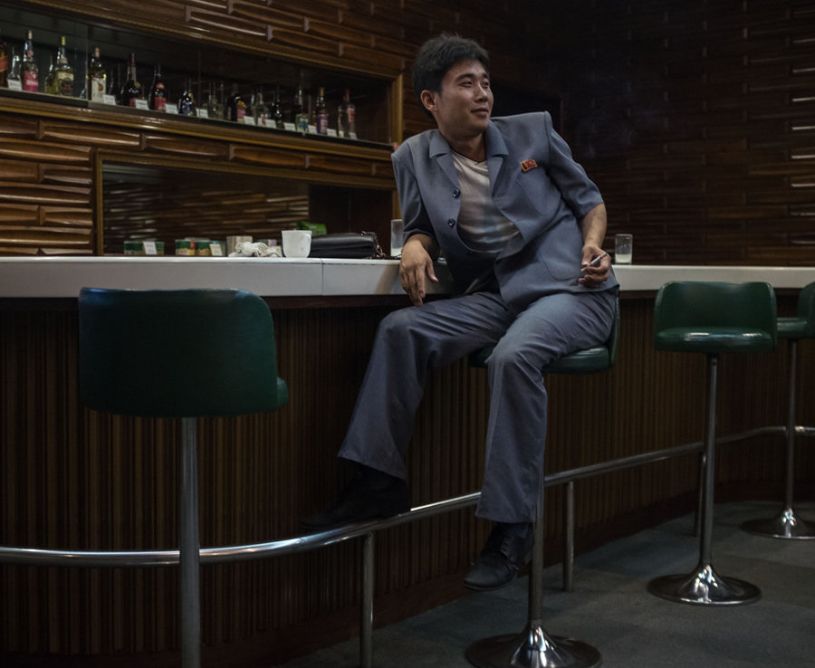 A man smokes a cigarette in a bar