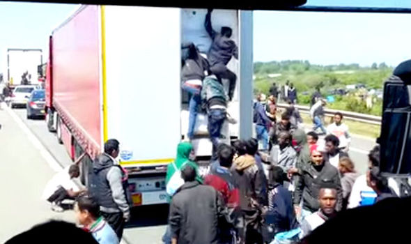Migrants climb into a lorry at Calais
