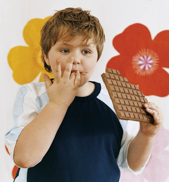 Boy eating a bar of chocolate