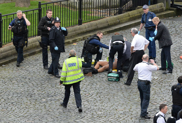 Police strip search a man on the ground