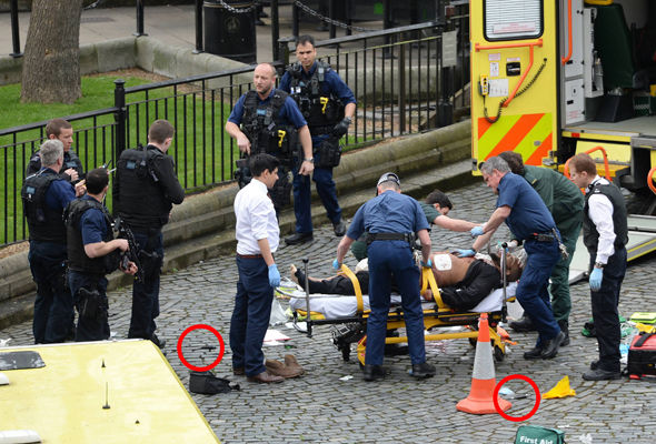 The man is taken into an ambulance as knives are seen on the ground
