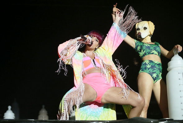 Lily Allen performs alongside a person with a dog's head