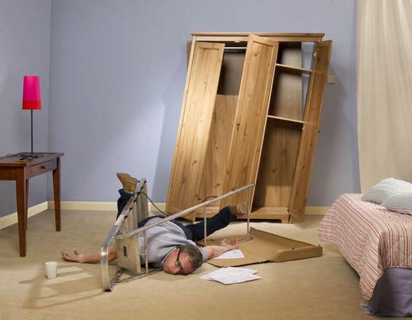 A man tangled in flatpack furniture