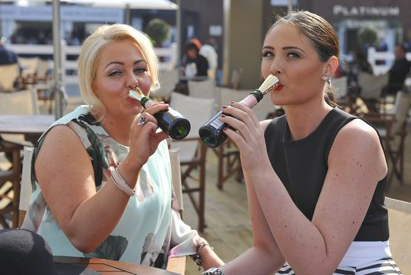 Two women hold champagne at the Grand National