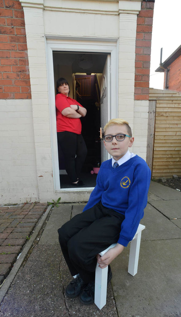 Bradley sits outside, alone - his mother watches