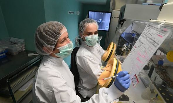 Medical scientists working at machines