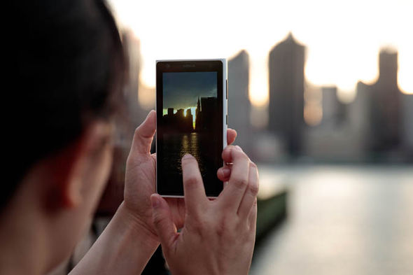 Person taking picture of Manhattanhenge