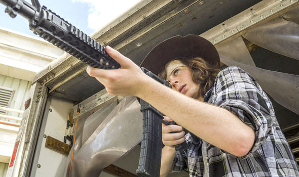 Carl Grimes takes aim at some of the undead in The Walking Dead