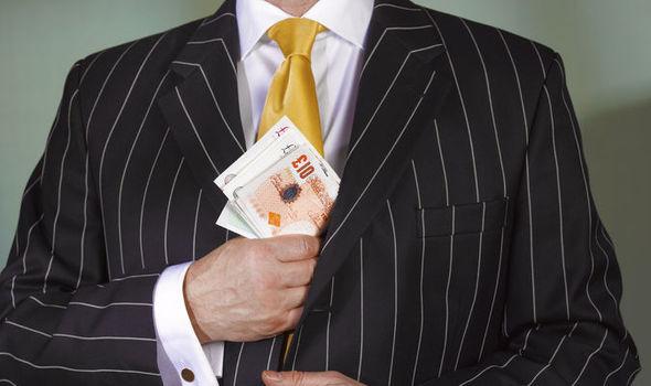 Suited man puts cash in jacket pocket