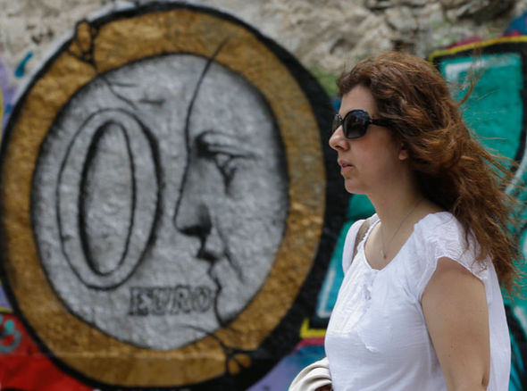 A woman stands in front of graffiti depicting a zero Euro coin in Athens