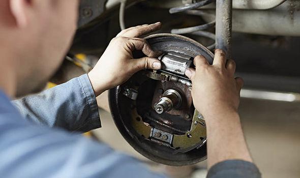 Car mechanic repairs brake disc