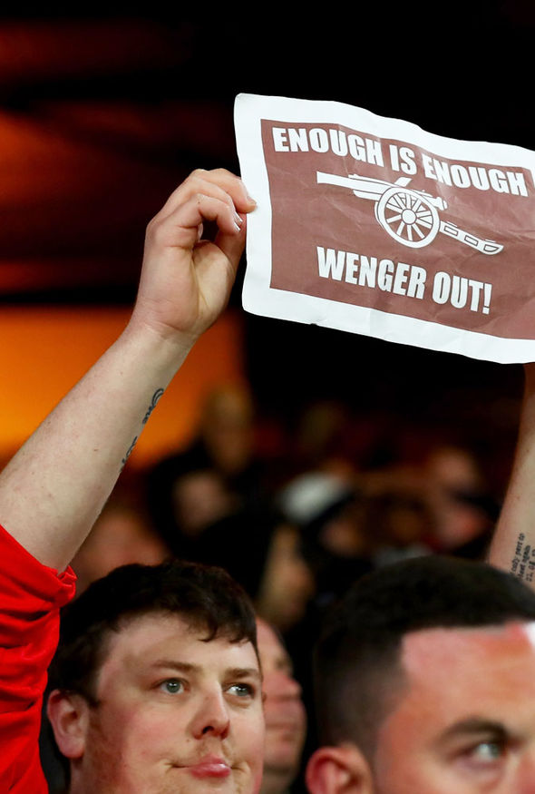 An Arsenal fan holding up a 'Wenger Out' banner