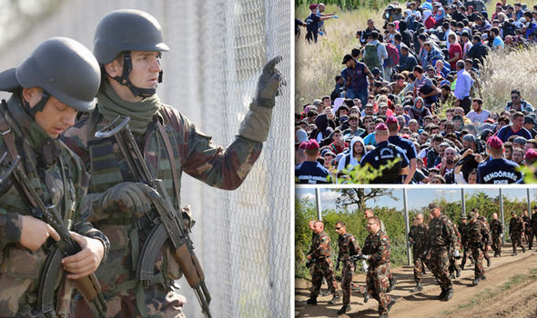 Hungarian soldiers march past the country's barbed wire border fence