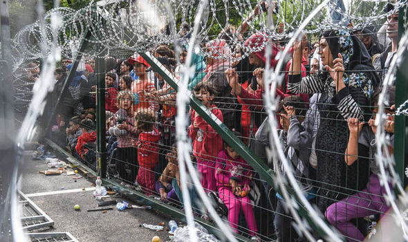Migrants at a fence in Hungary