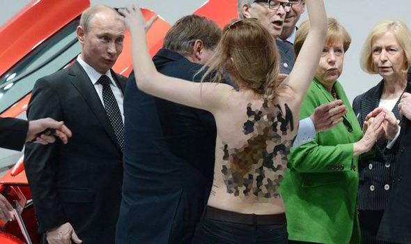 Angela Merkel and Vladimir Putin were confronted by a topless protestor in Hanover