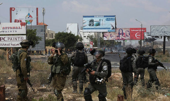 Israeli soldiers fire tear gas at Palestinian demonstrators during clashes with Israeli troops after a protest against the US Embassy move to Jerusalem