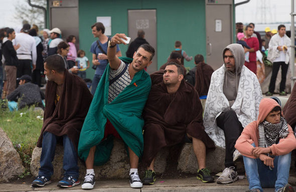 Migrants take a selfie while waiting for a bus to Austria