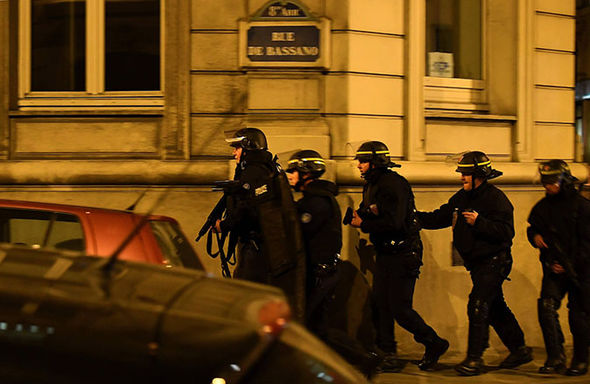 Police officers patrol near the site of a shooting at the Champs Elysees
