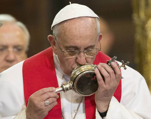Pope Francis kissing a sealed glass ampoule