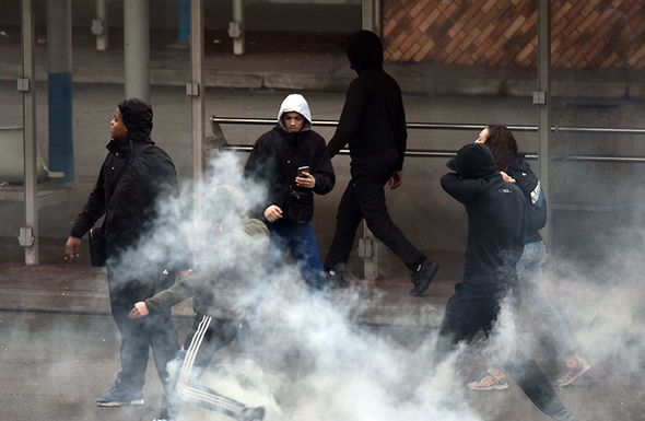 Young demonstrators kick gas canisters thrown by anti-riot police officers during scuffles