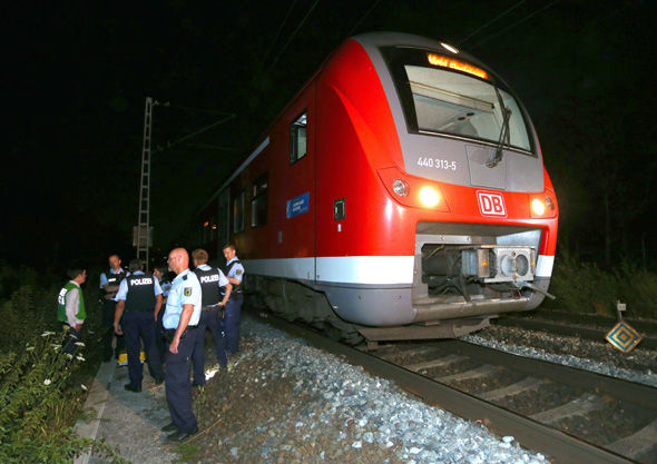 Police stand by the regional train on which a man allegedly wielding an axe attacked passengers in Wuerzburg, Germany