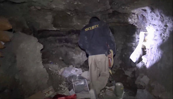 A member of Kurdish security forces shows a tunnel complex under the city of Sinjar,