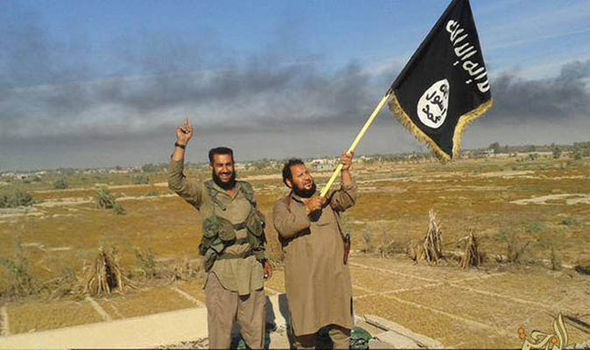 Two ISIS fighters hold a flag