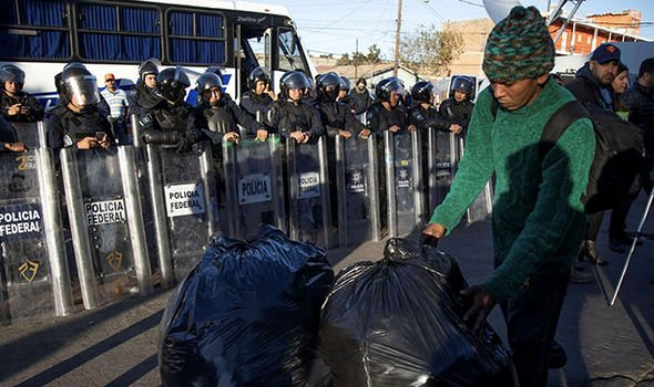 A migrant carries belongings in plastic bags as a group of migrants resisted leaving the warehouse