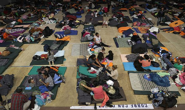 Migrants rest inside a temporary migrant shelter next to the US Mexico border