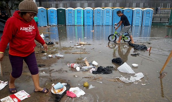 Migrants walk through a flooded area near portable toilets at a temporary shelter